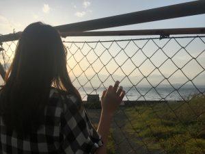 金網の外を眺める女性